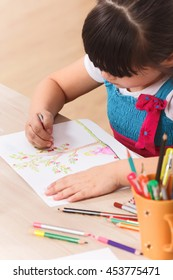 Closeup picture of little girl drawing picture with multicoloured pencils while sitting at the table at home.
