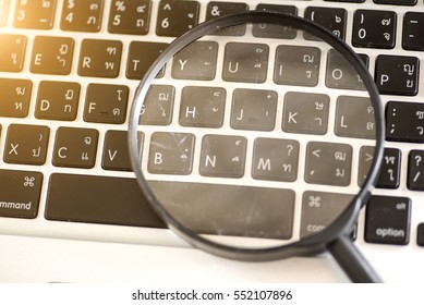 Closeup picture of a magnifying glass on a laptop keyboard, search, online shopping and business concepts.