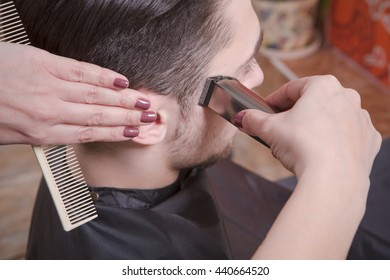 Closeup picture man's hairstyling and haircutting with hair clipper by barber girl or hairdresser in barber shop or hairdressing salon.