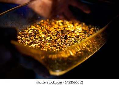 closeup picture of many ingots of melt gold, hot shiny metal pieces glowing, nobody