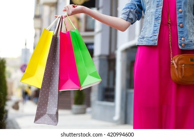 closeup picture of multi colored shopping bags with a hand