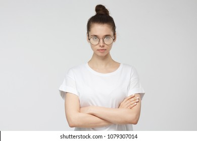 Closeup picture of pretty European Caucasian girl pictured isolated on grey background with white T-shirt and glasses, looking seriously at camera with arms crossed as if suspicious showing mistrust