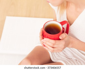 Close-up picture of red cup of tea in woman's hands. Lady sitting on the floor and enjoying hot tea.