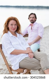 Close-up picture of red-haired woman smiling. Her man sitting on the chair behind her. People having rest at the beach near the sea.