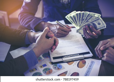 Closeup picture stack of banknotes US dollars in the hands of young men. In his right hand holding a pen and signing documents on business deals by having a third party become a witness.