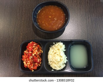 Closeup picture of Suki sauce and its topping which are a Chopped chilli, Garlic alley, lemonade are arranged on the wooden table