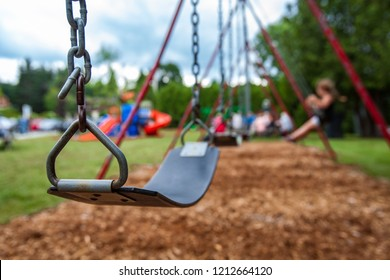 Closeup picture of a swing in a park for kids. Kids swigning in the blurry background - Picture taken on a warm summer day, with mulch ground instead of sand, and green lawn in the background