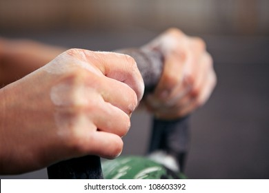 Closeup picture of two hands grabbing a kettle bell