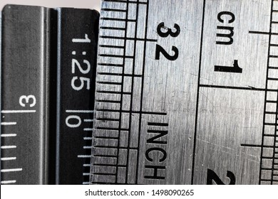 Close-up picture of two steel rulers showing the size difference between inches and centimeters. Conceptual british and metric system comparison.
