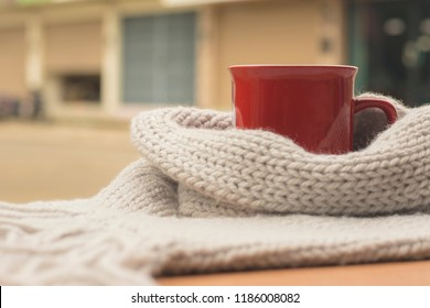 Closeup picture of warm scarf with cup of hot coffee on wooden, About winter.