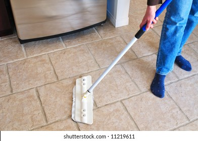 Close-up picture of woman's hand holding a mop cleaning kitchen floor