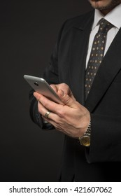 Closeup picture of young businessman holding mobile or smart phone in front of him. Handsome man in black suit looking at screen.