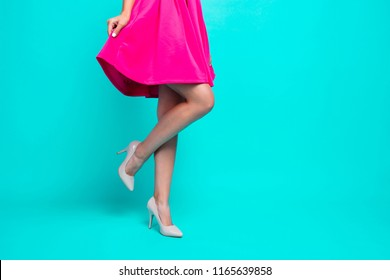 Close-up picture of young girl legs, pink fuchsia short mini dress, walking in high heels shoes. Copy space. Isolated over bright vivid turquoise teal background