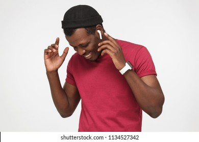 Closeup picture of young handsome African man isolated on grey background standing with earbuds on bending and moving during audio track he loves, smiling and feeling happiness of leisure moment