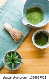 Close-up pictures of hot tea, green tea with Matcha tea powder, small cups on a wooden table