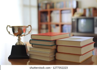 Close-up pictures of many books stacked on the table in the library. Trophies placed nearby selective focus and shallow depth of field