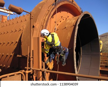 Closeup pictures of rope access miner  industrial rope access fitters, boiler maker wearing safety harness using twin rope abseiling inspection chute at construction mining site Perth, Australia