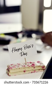 closeup of a piece of cake with a signboard with the text happy boss day written in it placed on a desk