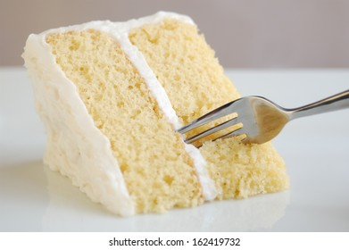 Closeup of a piece of fluffy yellow cake with white vanilla frosting, ready to eat.