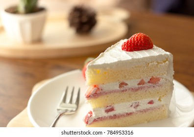 Closeup Piece of Strawberry Cake with whipped Cream serve on a white plate with fork and decoration fruit, Dessert Food on Wooden Table in the cafe