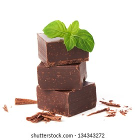 Closeup  pieces of chocolate parts and mint leaves isolated on white background