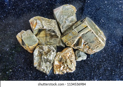 Close-up of pieces of raw pyrite crystals on dark granite polished slab. Texture of crystals of pyrite. Pyrite crystals geological mineral background. Selective focus