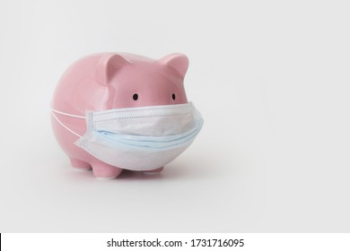 Close-up piggy bank with medical mask on face is standing on white background. Concept of passive money income during the crisis and coronavirus pandemic. Advertising space