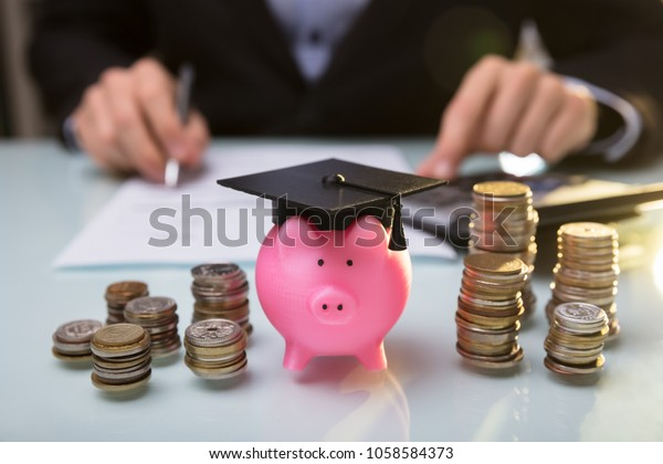 Close-up Of Piggy Bank Wearing Graduation Hat And Stacked Coins In Front Of Businessperson