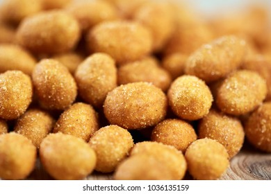 Closeup of a pile of coated peanuts on a wooden board