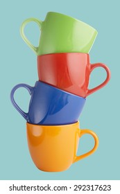 Closeup of pile of colorful cups on blue background