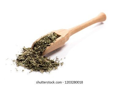 Close-up of pile of dried herbs,  garden lovage leaves in a wooden spoon on white background