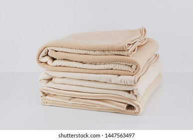 Closeup pile folded natural beige cotton blanket for kid on white background