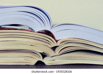 Closeup of a pile of open books on a table. School, College, University concept. Copy space.
