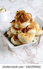 closeup pile of pierogies with sour cream caramelized onions and a fork