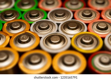 Closeup of pile of used alkaline batteries. Close up colorful rows of selection of AA batteries energy abstract background of colorful batteries.