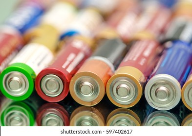 Closeup of pile of used alkaline batteries. Closeup colorful rows of selection of storage batteries energy background of colorful storage batteries. Alkaline battery aa size. Several batteries in rows