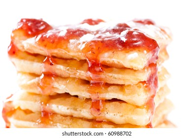 Closeup of pile of waffles with honey, strawberry jam and sugar on white background