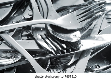 closeup of a pile of wet knifes, forks and spoons
