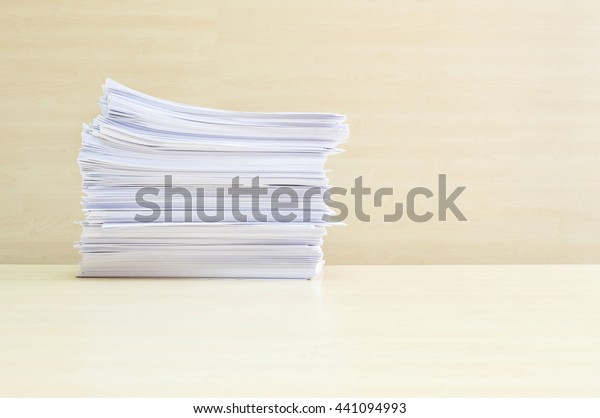 Closeup pile of work paper on blurred wooden desk and wall textured background in the meeting room under window light , hard work concept
