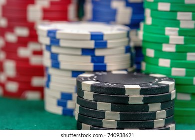 Closeup of piles of casino chips on green table cloth
