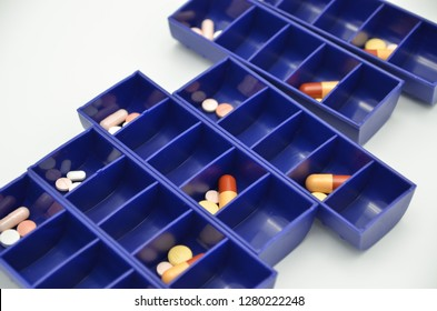 A closeup of a pill dispenser. Dispensers are used as an aid in remembering to take medication at the right time of day to help prevent mistakes in long term medication.