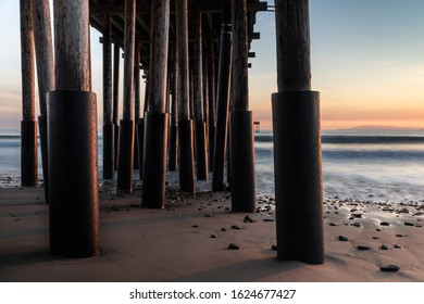 Closeup of pillars, Ventura Pier, Ventura, California at sunset. sand and rocks in foreground; silky ocean, colored sky beyond.