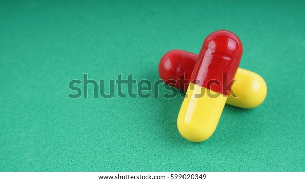 Closeup of pills or capsules with isolated green background.Selective focus.