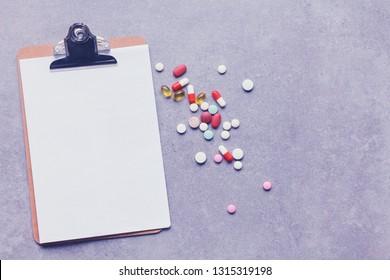 Closeup of a pills, stethoscope on an rx prescription.