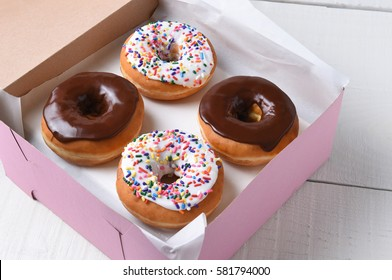 Closeup of a pink bakery box with four fresh donuts, two chocolate and two frosted with sprinkles.