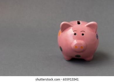 Closeup pink ceramic piggy bank on dark background