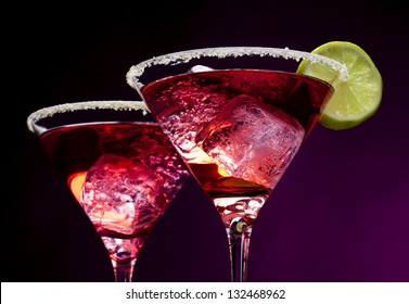 Closeup of pink cocktails in martini glasses with sugared edges, ice cubes and lime slices