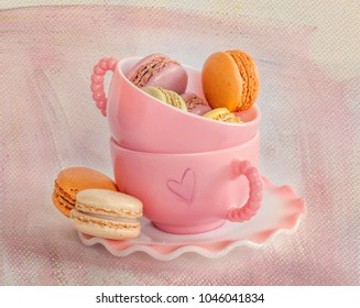 Closeup of Pink Cups and French Macaroons on a Textured Background