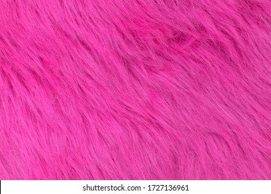 Close-up pink faux wool with long pile. Artificial fur texture, useful as background.