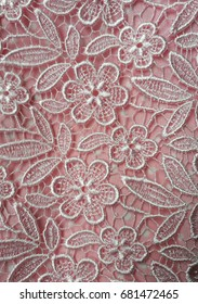 Closeup of pink lace texture with flower pattern background.